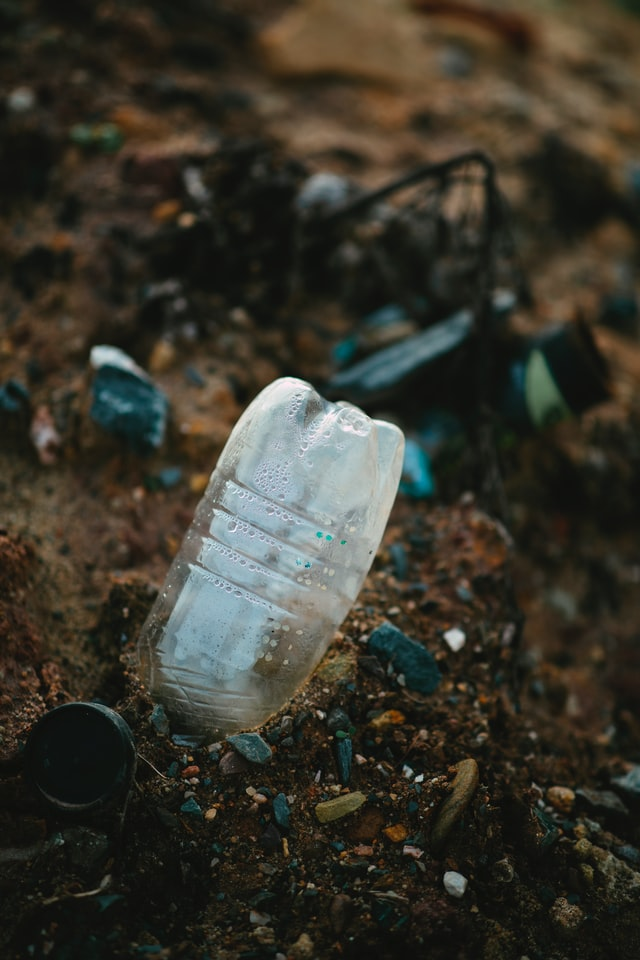 A plastic bottle in the dirt, illustrating non-biodegradable waste.